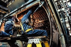 A man working on boiler tube repair.