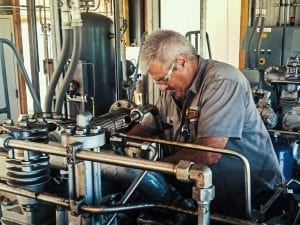 Rasmussen Mechanical employee working on an air compressor