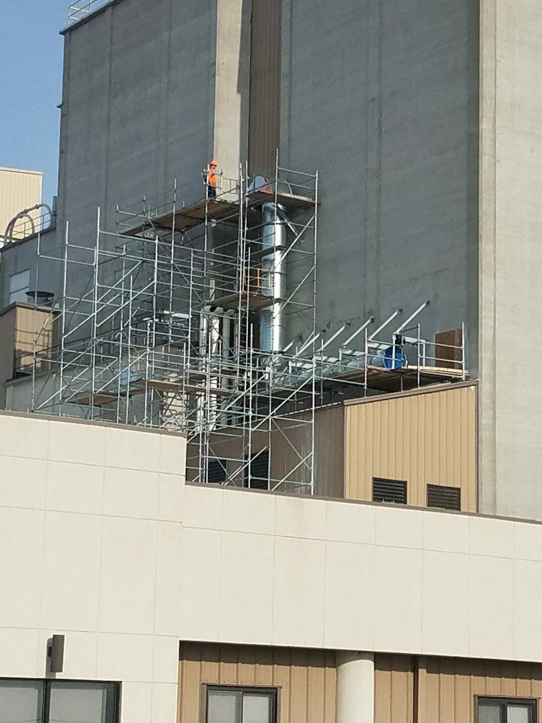 Service technician on scaffolding set up outside a building during a plant shutdown.