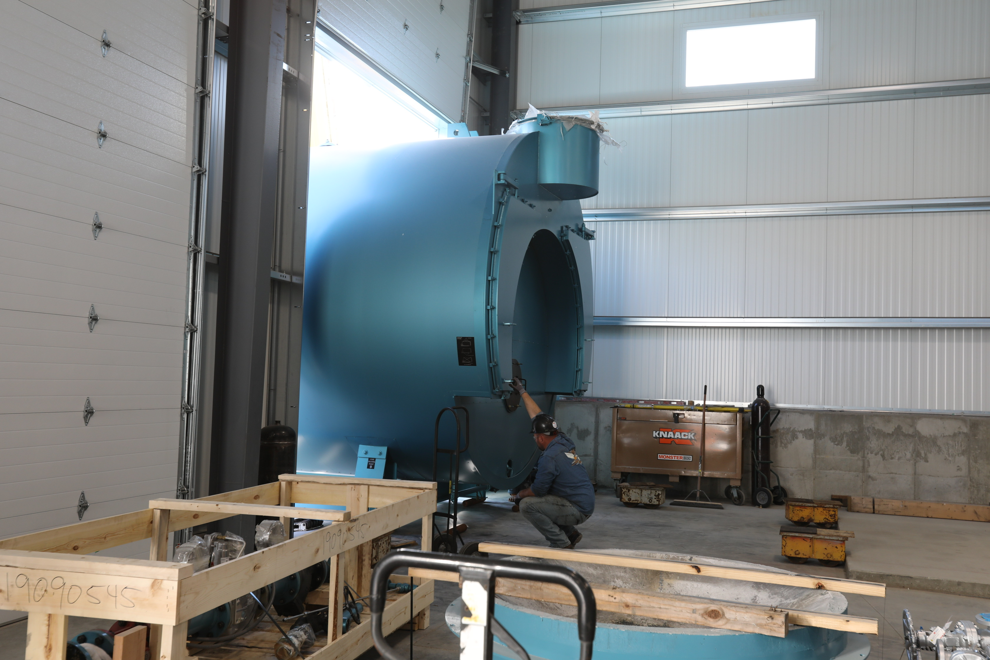 Technician helping to guide a 1500 HP Superior boiler into a new building.